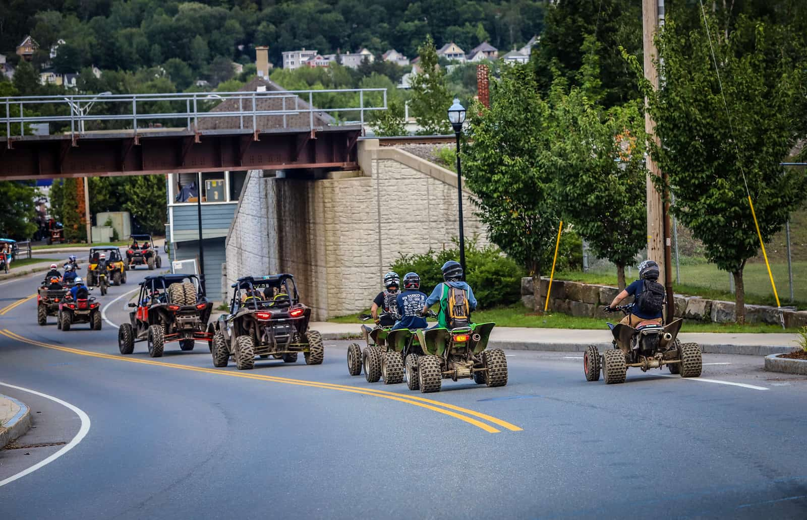 ATVs driving on the street in Berlin, NH at the Jericho ATV Festival